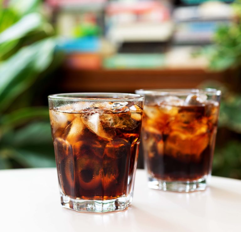 a glass of cola with iced on white table