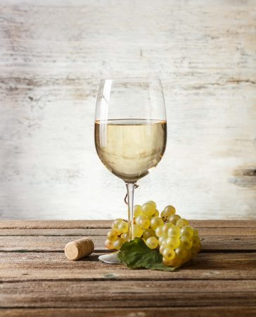 Wineglass with white wine on wooden table